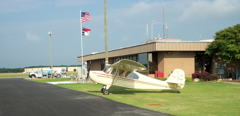 Lumberton Municipal Airport building with a plane out front.