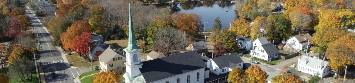 Mansfield, Massachusetts aerial with a church in the foreground and a pond beyond.