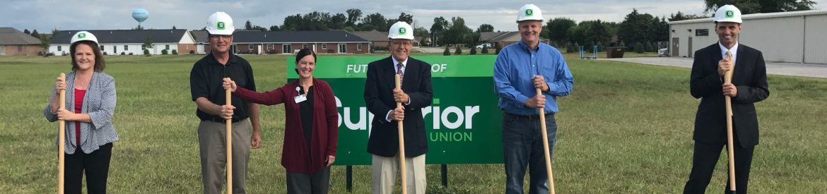 Superior Credit Union Coldwater Groundbreaking with 6 people standing with shovels wearing helmets for a groundbreaking ceremony