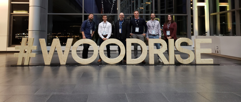 Element5 group of people posing for a photo with a wooden sign in front, saying #woodrise