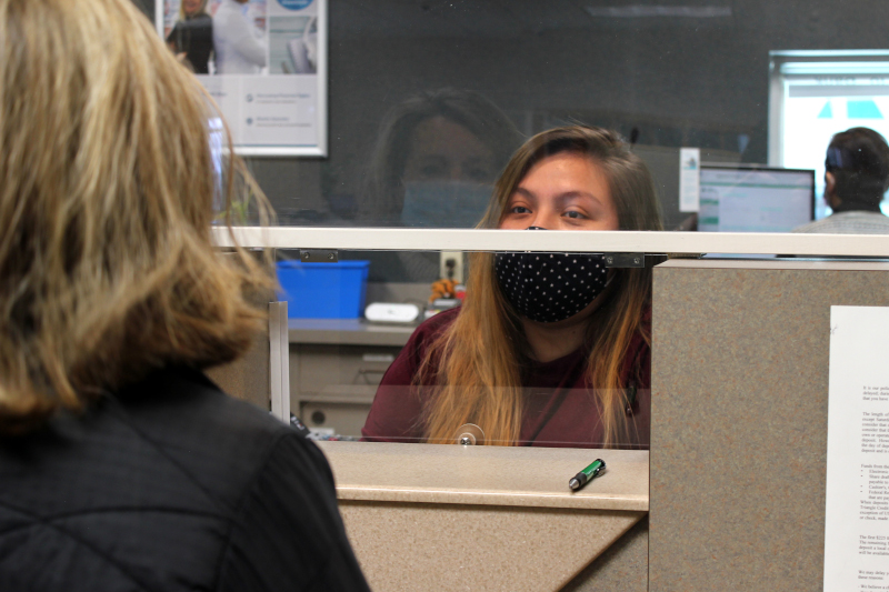 A Triangle Credit Union teller assist a member through plexiglass in Nashua, NH.