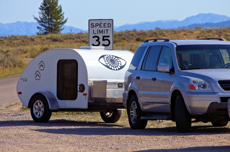 The Recreation Vehicle Industry Association RVIA teardrop camper on the side of a road behind car.