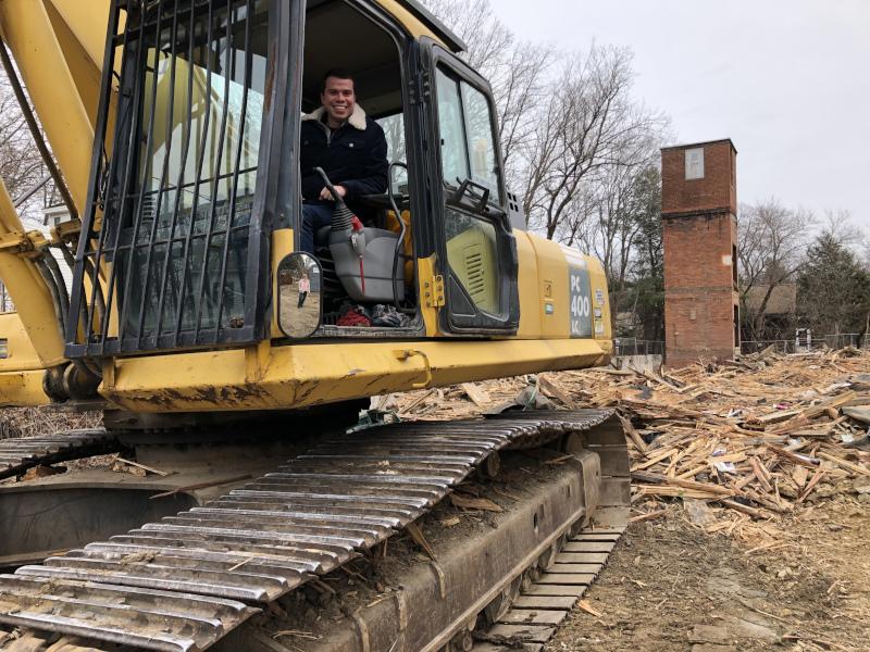 Gardner, Massachusetts Rock St Demo showing a man in a excavator