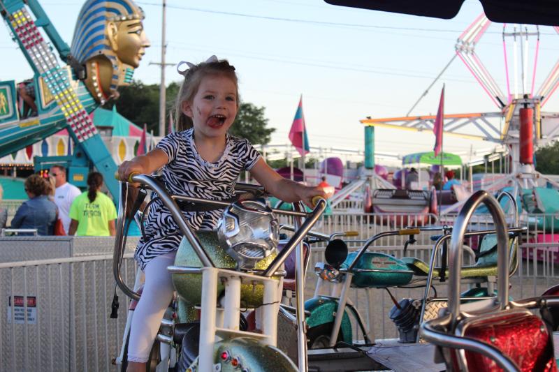 Washington, Illinois Girl riding a ride at Cherry Fest