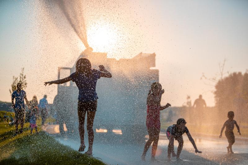Cottage Grove, Minnesota kids playing in water from a fire truck.