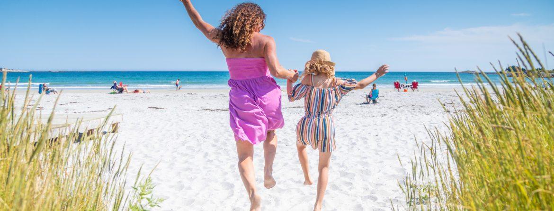 Shelburne, Nova Scotia white sand beach. Two women skipping on the beach facing away towards the ocean